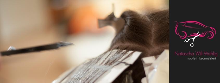 Auftragen der Blondierung auf die Haare beim Strähnen. Mit Firmenlogo.