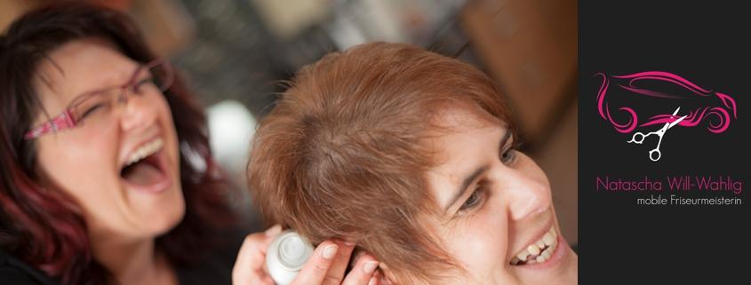 Friseurin und Kundin mit fertig gestylten Haaren lachen. Mit Firmenlogo.